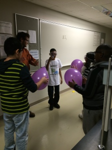 Alex uses balloons to help students visualize different atom sizes and how this affects their reactivity.